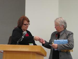 Chapter President Barbara Buchholz presents Chancellor Carmen Farina with a gift membership and gold clad pin.