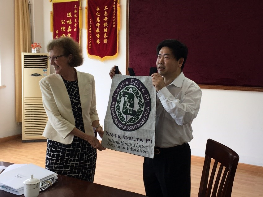 KDP Counselor Dr. Chen Xaioda proudly displays the KDP banner which will hang in the school's conference room.